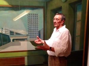 """Giacinto Di Pietrantonio, critico d'arte, curatore della mostra davanti al grande olio su tela di Arduino Cantafora """"la Città Banale"""" (1945)"""